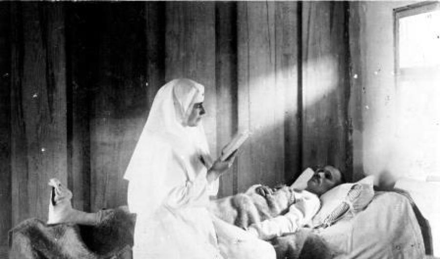 Regina Maria citind la căpătâiul unui bolnav. Fotografie din timpul Primului Război Mondial